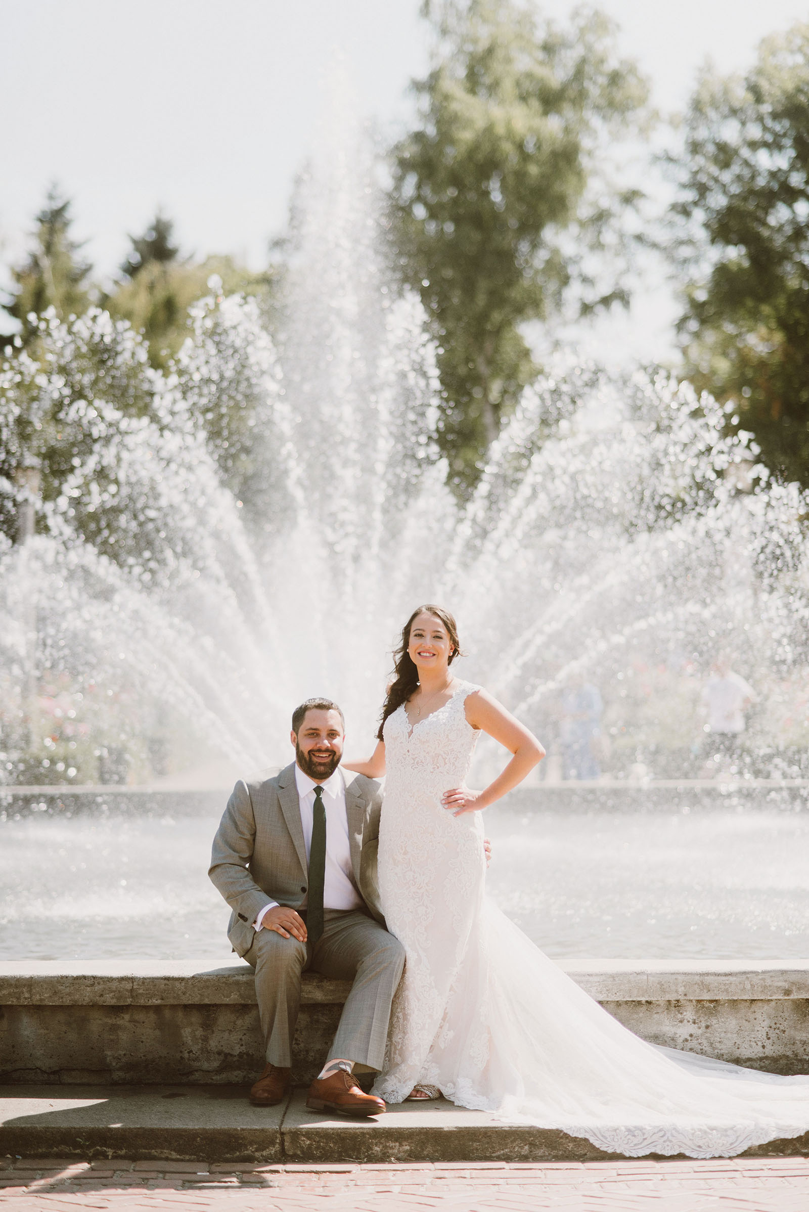 Bride and Groom posing in front of the water fountain in Peninsula Park