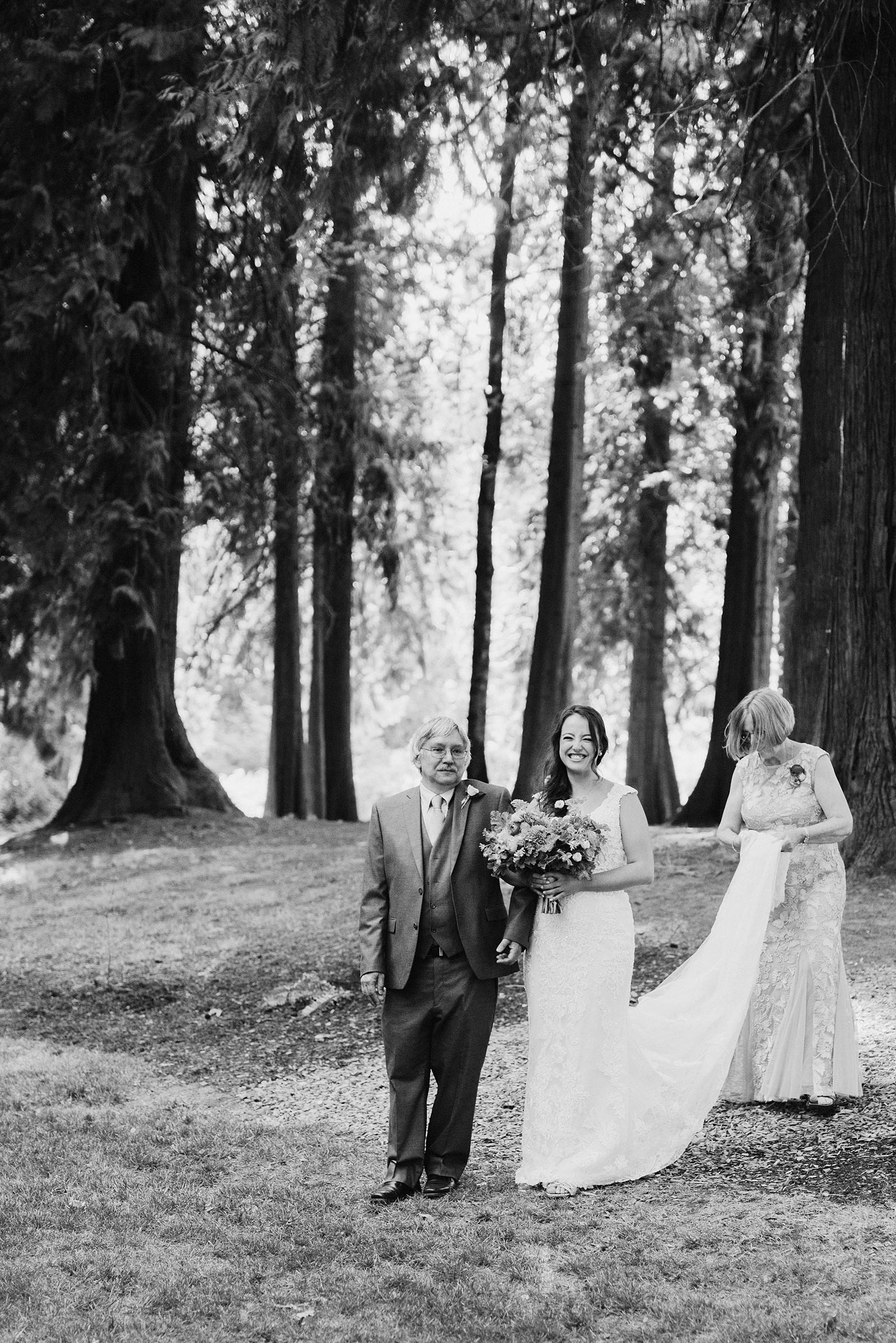 Bride walking down the aisle with her father and mother at a Cedarville Lodge Wedding