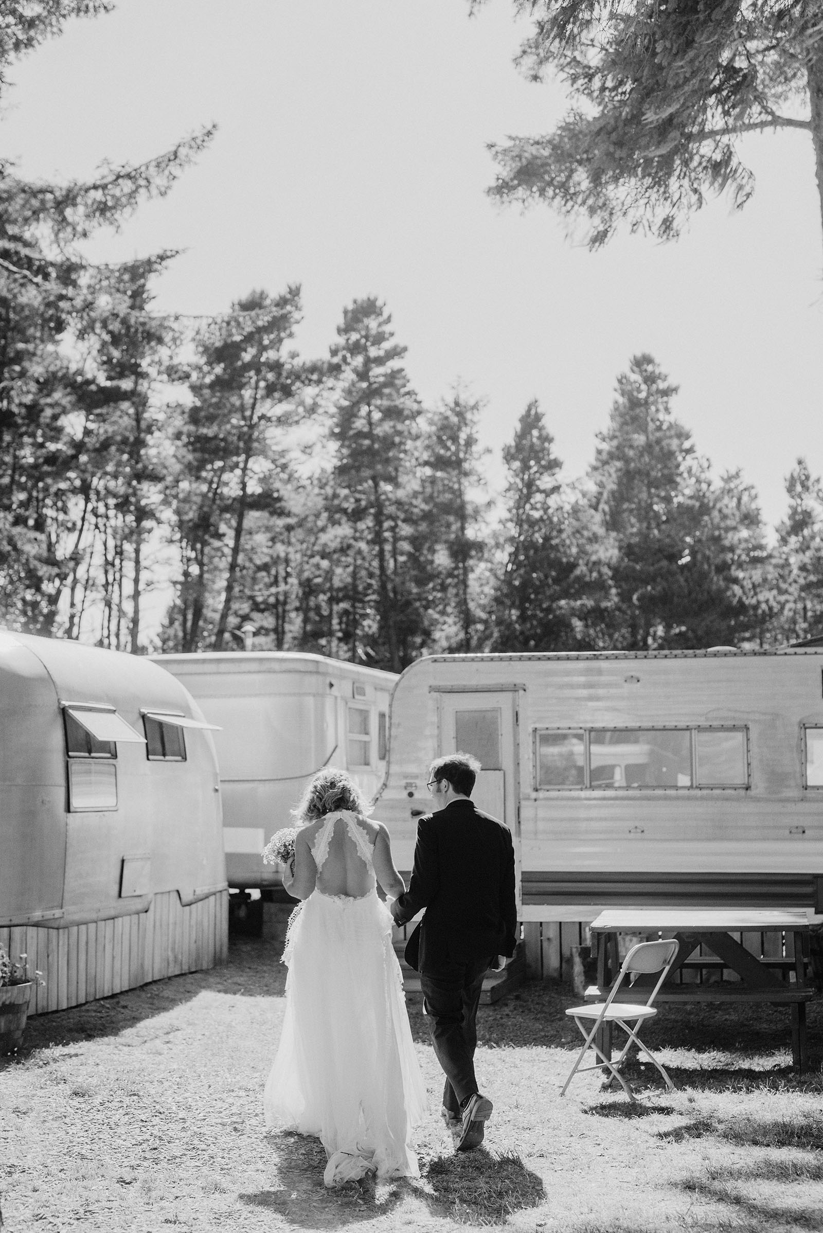 Bride and Groom walking behind the trailers at a SouWester Wedding in Seaview, WA