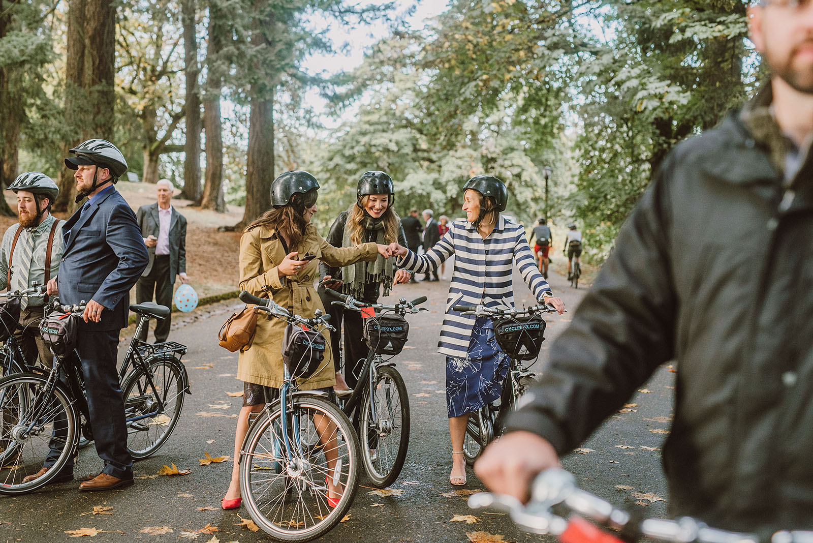 wedding guests fist bumping before a bike parade on Mt Tabor - portland wedding photography